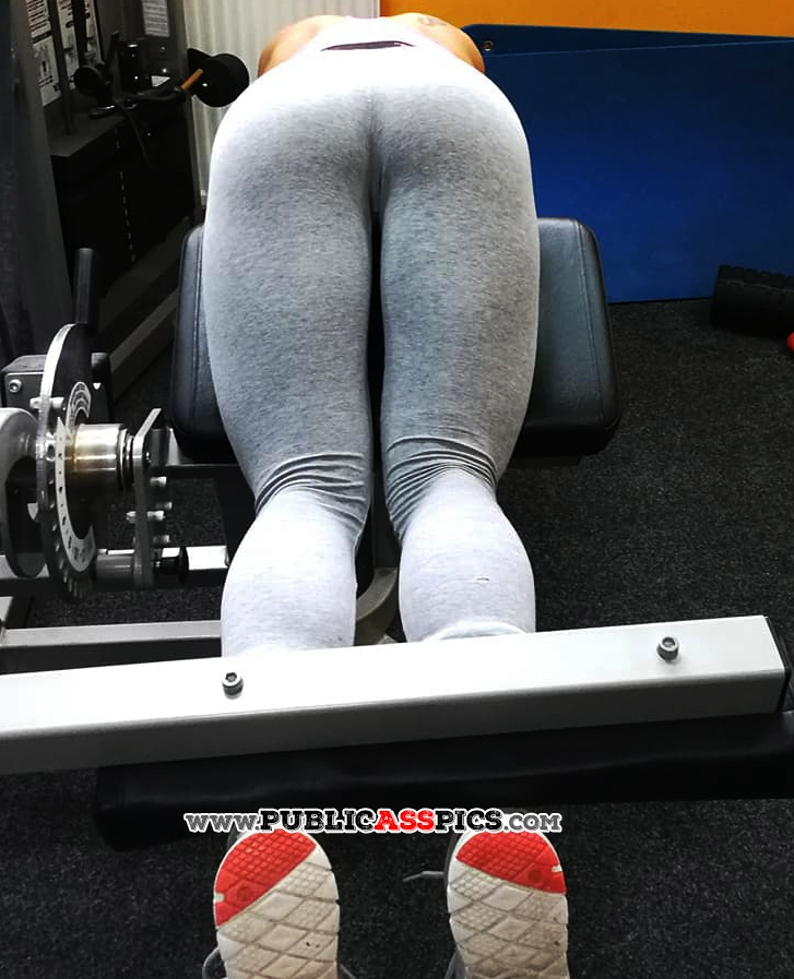 Hot fitness girl bent over while exercising her legs