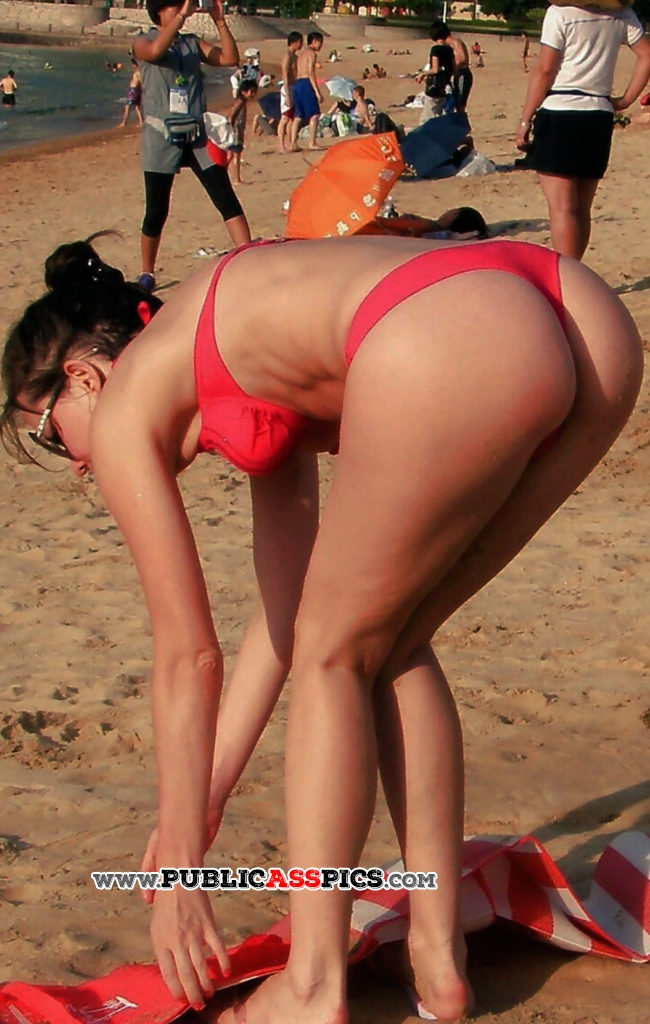 Amazing milf in red thong bikini bends over on beach
